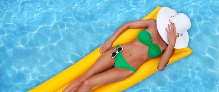 Girl floating in crystal clear pool water